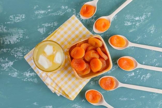 Getrocknete aprikosen in holzteller und löffel mit saft draufsicht auf gips und picknicktuch