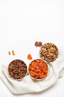 Getrocknete aprikosen, rosinen, walnuss in tassen auf einer serviette stehend