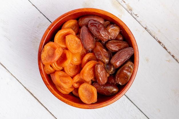 Getrocknete aprikosen und datteln in einer holzschale mit datteln