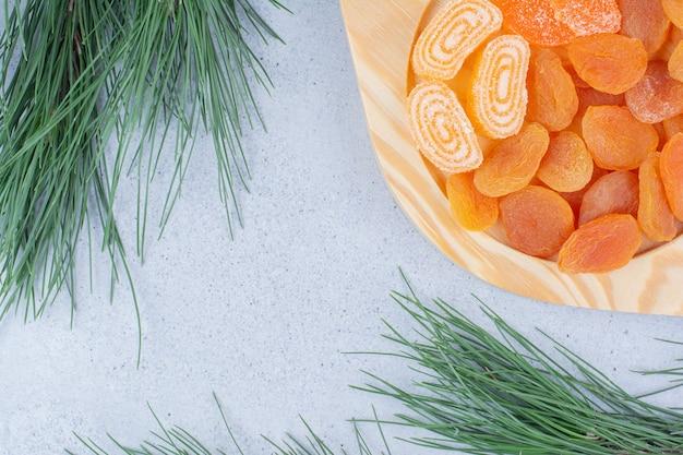 Getrocknete aprikosen und marmeladen auf holzteller.