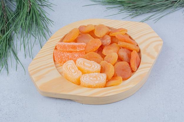 Getrocknete aprikosen und marmeladenbonbons auf holzteller.