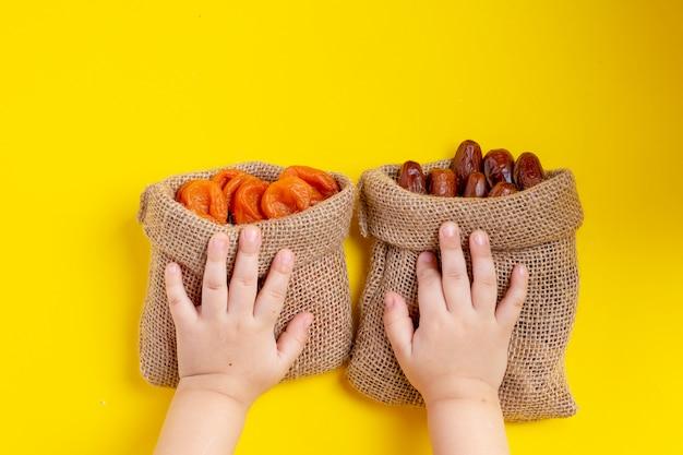 Getrocknete aprikosenfrüchte und datteln in segeltuchtaschen.