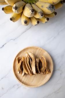 Getrocknete banane auf marmor mit echter banane