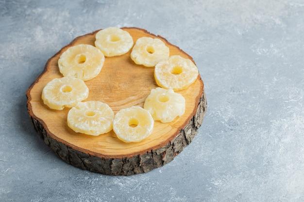 Getrocknete bio-ananasringe auf holzstück gelegt