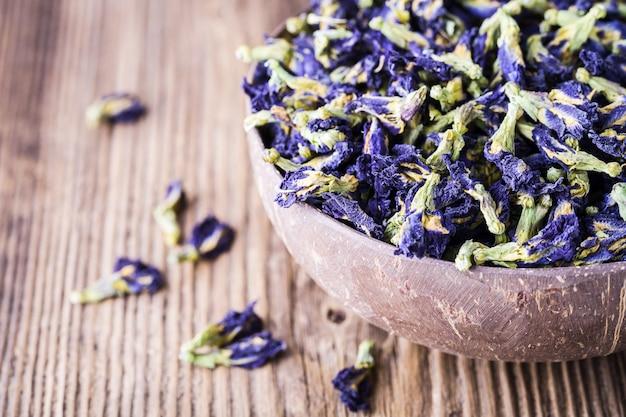 Getrocknete blaue schmetterlingserbsenblumen auf hölzernem hintergrund.