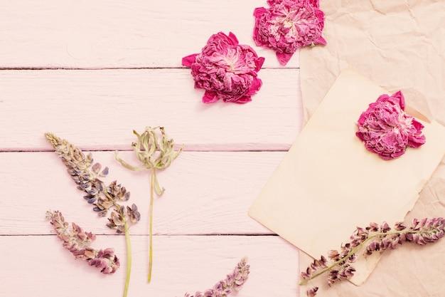 Getrocknete blumen auf rosa hölzernem hintergrund
