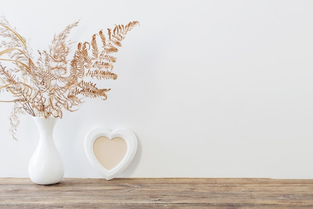 Getrocknete blumen in der vase auf holztisch auf weißem hintergrund