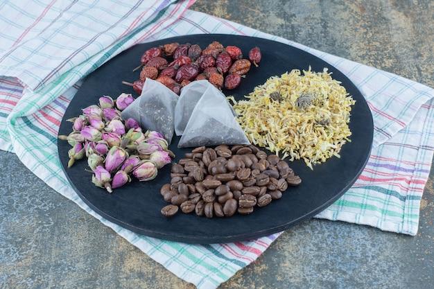 Getrocknete blumen, kaffeebohnen, hagebutten und teebeutel auf schwarzem brett.