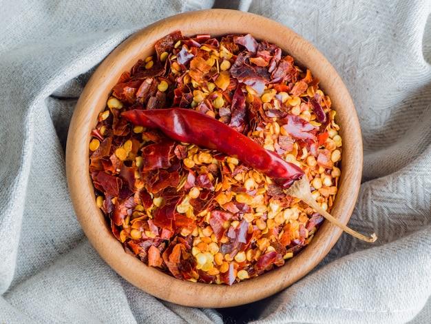 Getrocknete chili-pfeffer-flocken in holzschale mit leinentuch. getrocknete und zerkleinerte früchte von capsicum frutescens