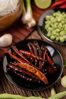 Getrocknete chilis in einem schwarzen teller mit linsen gebraten. gurken und knoblauch werden auf den holztisch gelegt