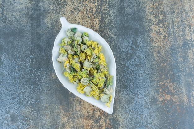 Getrocknete chrysanthemenblüten auf blattförmigem teller.
