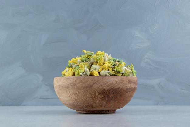 Getrocknete chrysanthemenblüten in holzschale.