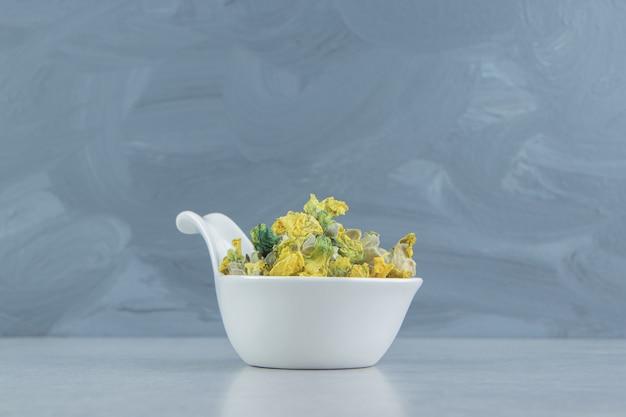 Getrocknete chrysanthemenblüten in weißer schüssel.