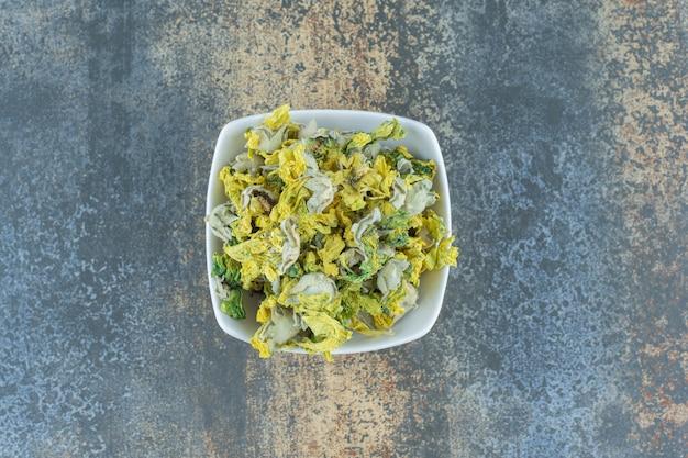 Getrocknete chrysanthemenblume in weißer schüssel.