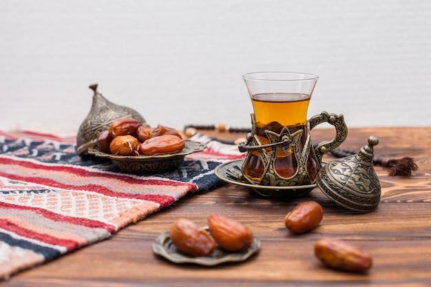 Getrocknete dattelfrucht mit einem glas tee