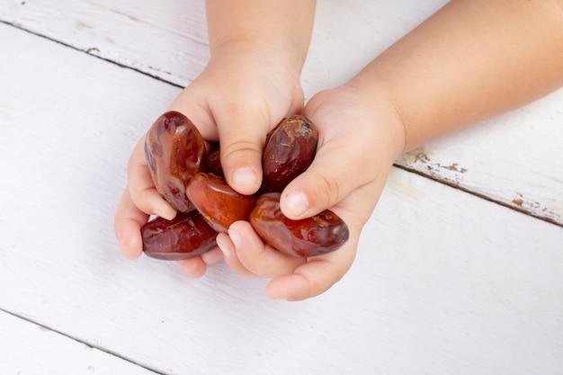 Getrocknete dattelfrüchte in kinderhänden auf holz