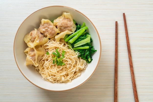 Getrocknete eiernudeln mit wan-tan oder schweineknödel ohne suppe nach asiatischer art