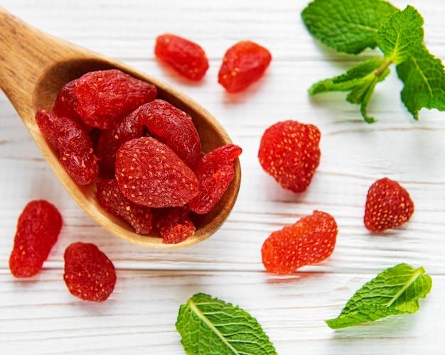 Getrocknete erdbeeren im löffel auf einem weinlesehintergrund