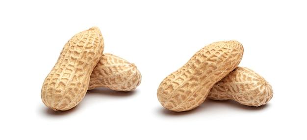 Getrocknete erdnüsse in schalennahaufnahme lokalisiert auf weißem hintergrund.