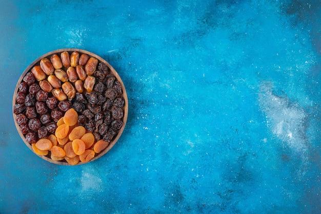 Getrocknete früchte auf einem brett, auf dem blauen tisch.