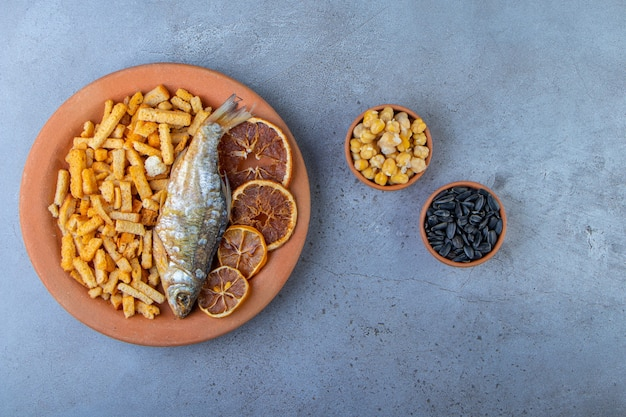 Getrocknete früchte, fisch und croutons auf einem teller neben kichererbsen und saatschalen, auf der marmoroberfläche.