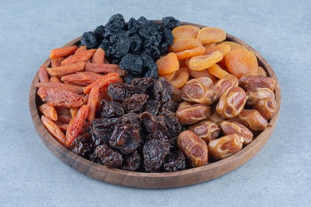 Getrocknete früchte im holzbrett auf dem marmortisch.