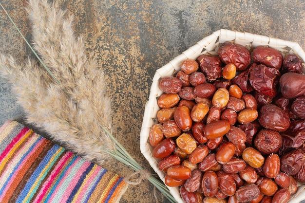 Getrocknete früchte mit bunter tischdecke auf marmorhintergrund. hochwertiges foto