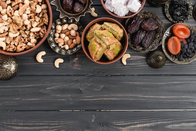 Getrocknete früchte; nüsse; termine; lukum und baklava auf ramadan über dem holzschreibtisch