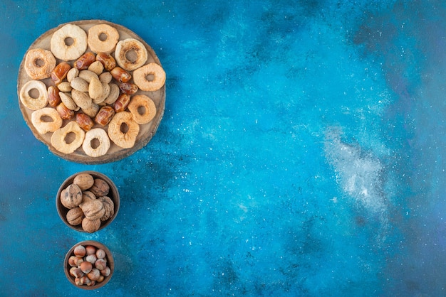 Getrocknete früchte und leckere nüsse auf einem brett, auf dem blauen tisch.