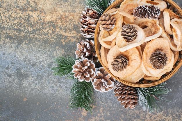 Getrocknete früchte und tannenzapfen in der holzschale auf marmorhintergrund. hochwertiges foto
