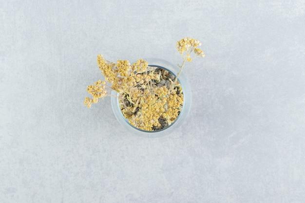 Getrocknete gelbe blumen aus der glasschale.