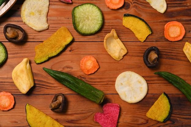 Getrocknete gemüsechips mit grünem rettich, okra, karotten, kürbis, rote beete und shiitake-pilzen auf holzhintergrund.