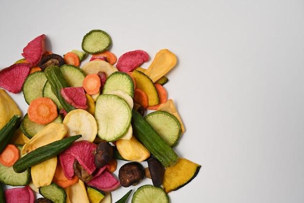 Getrocknete gemüsechips mit okra, karotten, kürbis, rote beete und shiitake-pilzen auf weißem hintergrund.