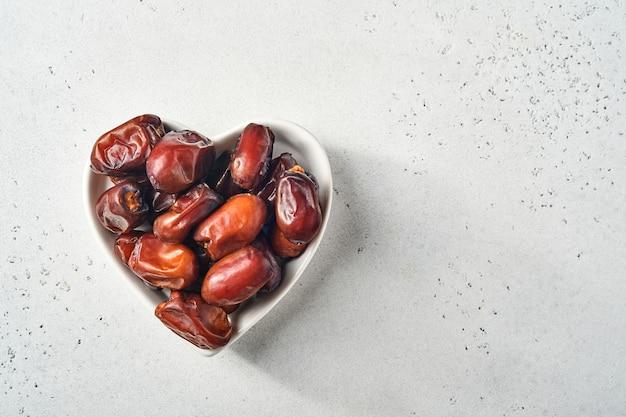 Getrocknete geschnittene dattelfrüchte in herzförmiger keramikplatte auf weißem hintergrund snack veganes zuckerfreies essen