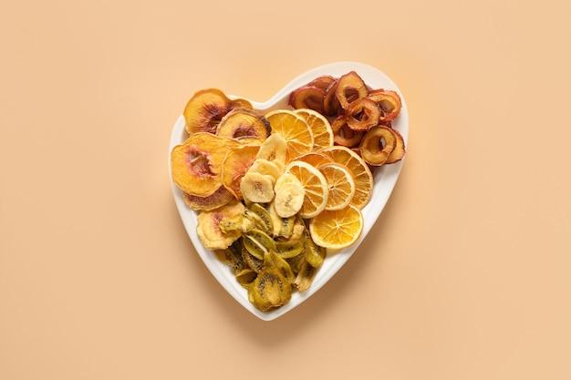 Getrocknete geschnittene pflaumen-kiwi-pfirsich-fruchtchips auf beige