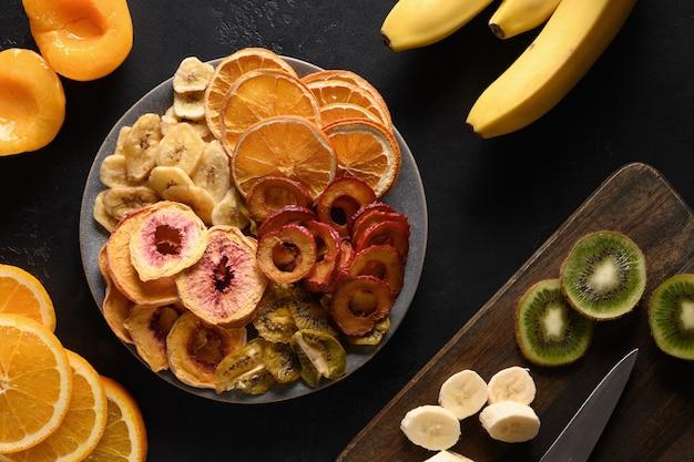 Getrocknete geschnittene pflaumen-kiwi-pfirsich-fruchtchips auf schwarz