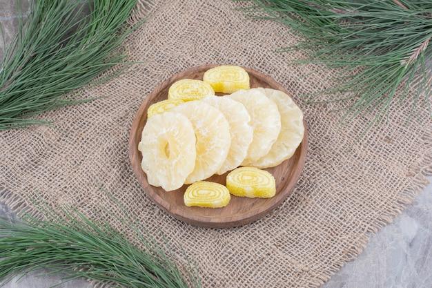 Getrocknete gesunde ananas mit süßer marmelade auf holzteller.