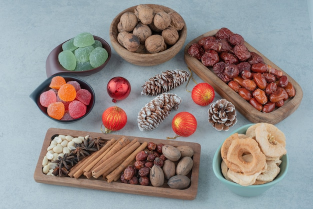 Getrocknete gesunde früchte auf holzteller mit weihnachtsspielzeug. hochwertiges foto