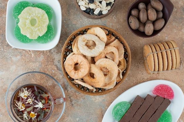 Getrocknete gesunde früchte mit marmelade und einer tasse kräutertee