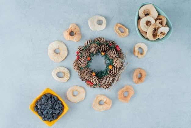 Getrocknete gesunde früchte mit tannenzapfen und weihnachtskugeln. hochwertiges foto