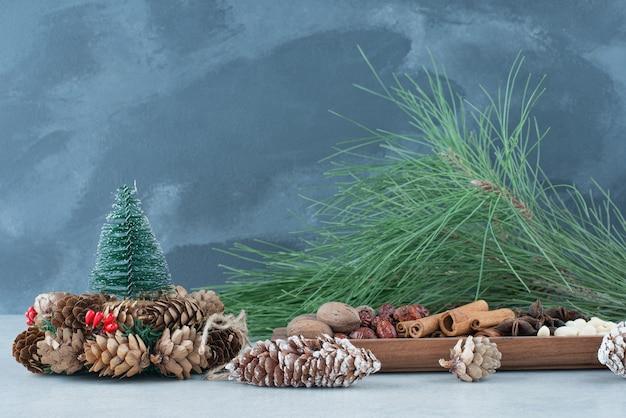 Getrocknete gesunde früchte mit weihnachtskranz aus tannenzapfen. hochwertiges foto