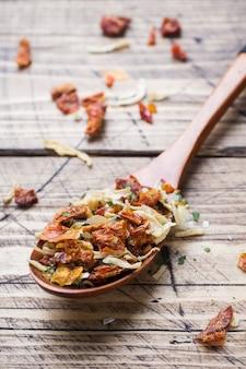 Getrocknete gewürze, sonnengetrocknete tomaten, getrocknete karotten, basilikum und provenzalische kräuter in einem holzlöffel auf einem holztisch. kopieren sie platz.