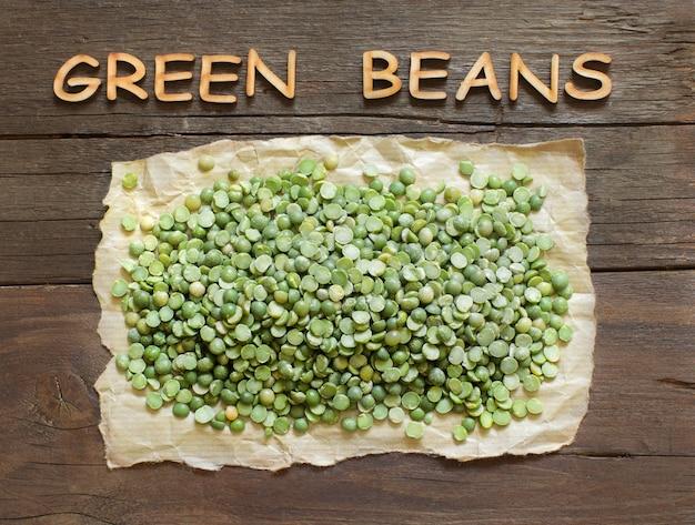 Getrocknete grüne erbsen mit einem wort auf holztisch