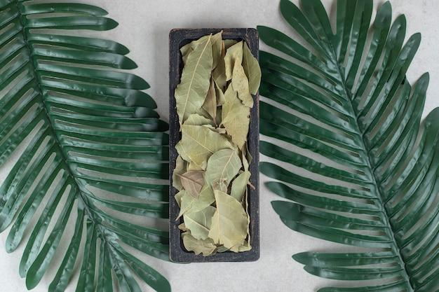 Getrocknete grüne lorbeerblätter auf einem holzteller.