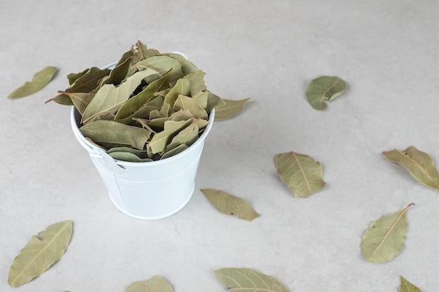 Getrocknete grüne lorbeerblätter in einer keramikschale.