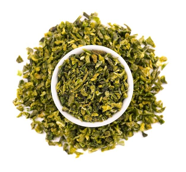 Getrocknete grüne paprikaflocken mit samen in der schüssel, lokalisiert auf weißem hintergrund. gehackte jalapeno, habanero oder chilischote. gewürze und kräuter. ansicht von oben.