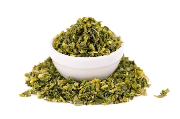 Getrocknete grüne paprikaflocken mit samen in der schüssel, lokalisiert auf weißem hintergrund. gehackte jalapeno, habanero oder chilischote. gewürze und kräuter.