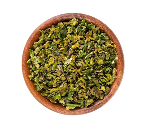 Getrocknete grüne paprikaflocken mit samen in holzschale, isoliert auf weißem hintergrund. gehackte jalapeno, habanero oder chilischote. gewürze und kräuter. ansicht von oben.