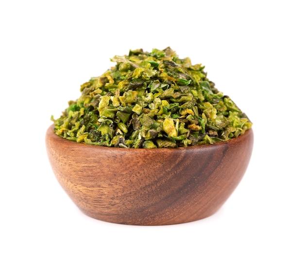 Getrocknete grüne paprikaflocken mit samen in holzschale, isoliert auf weißem hintergrund. gehackte jalapeno, habanero oder chilischote. gewürze und kräuter.
