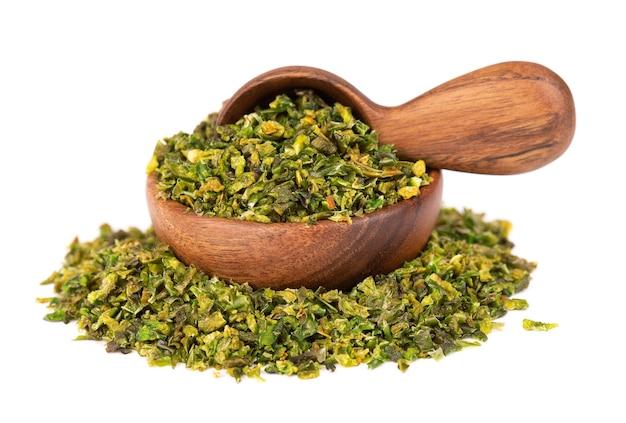 Getrocknete grüne paprikaflocken mit samen in holzschale und löffel, isoliert auf weißem hintergrund. gehackte jalapeno, habanero oder chilischote. gewürze und kräuter.